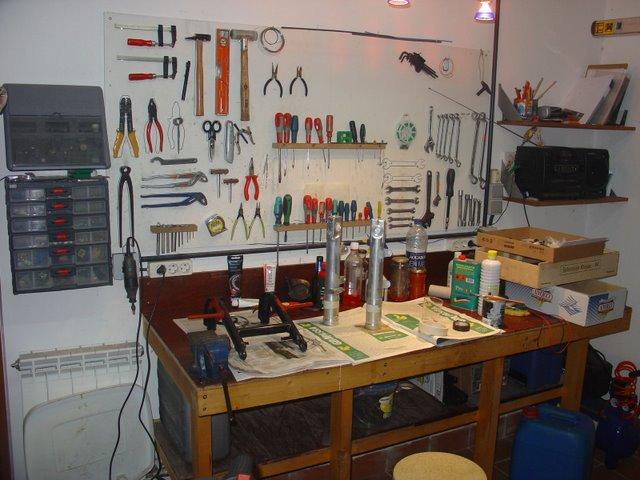 """Y entramos en el taller, encontrándonos en un lateral un banco de trabajo """"hand made"""" a partir de un cabezal de cama. El imprescindible tablero para colgar herramientas, y el arradio."""
